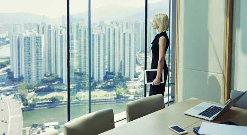 Women CEO looks out of office window