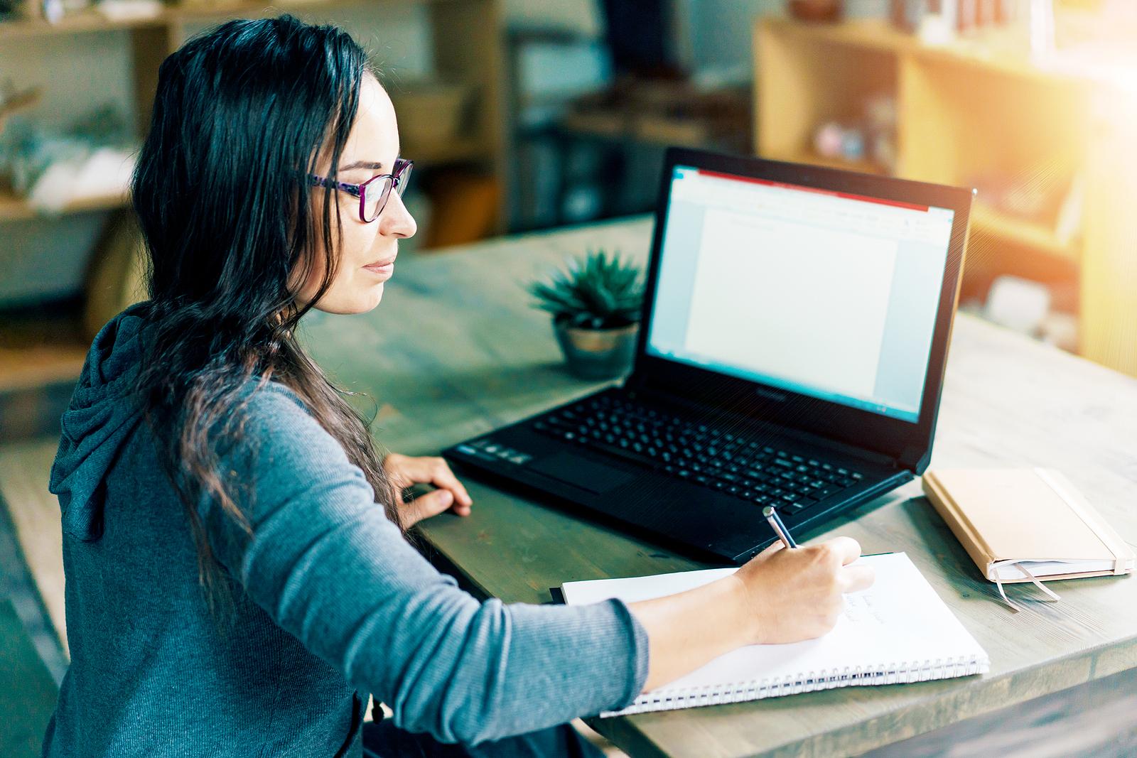 Women writing essay on laptop