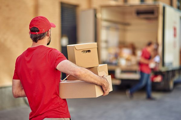 Deliveryman carrying parcels to van