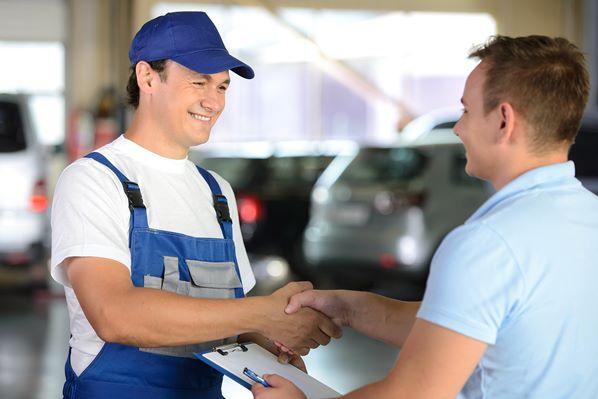 Garage mechanic serving customer